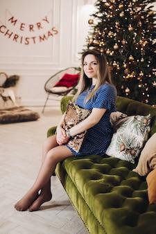 Bella donna si siede sul divano vicino all'albero di natale