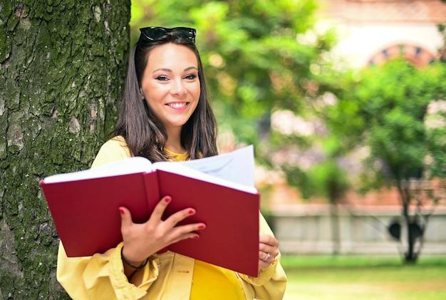 Bella studentessa che legge un libro all'aperto