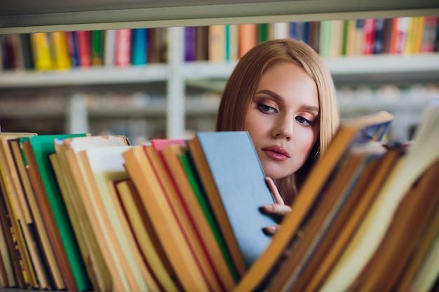 Bella studentessa in biblioteca universitaria
