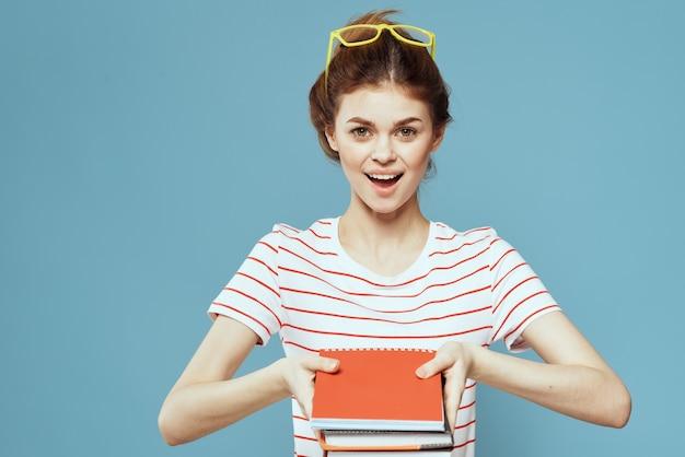 Bella studentessa con taccuini e in vetri gialli su un istituto di scienze dell'educazione blu.