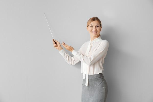 Bella insegnante femminile con puntatore sul muro chiaro