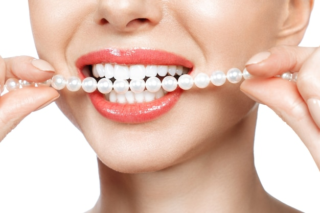 I bei denti femminili sorridono e la collana della perla, sbiancamento dei denti di concetto di salute dentale. dentale