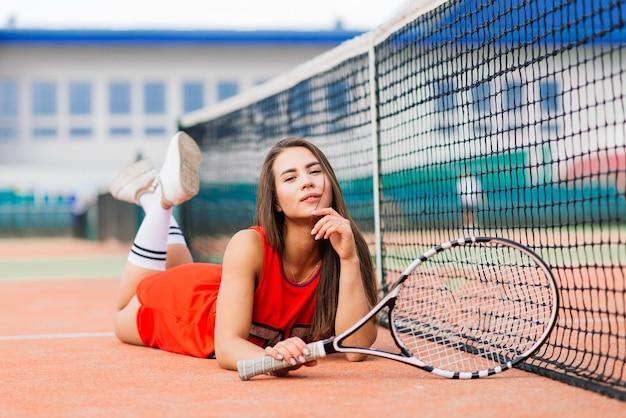 Bello giocatore di tennis femminile sul campo da tennis in vestito rosso.