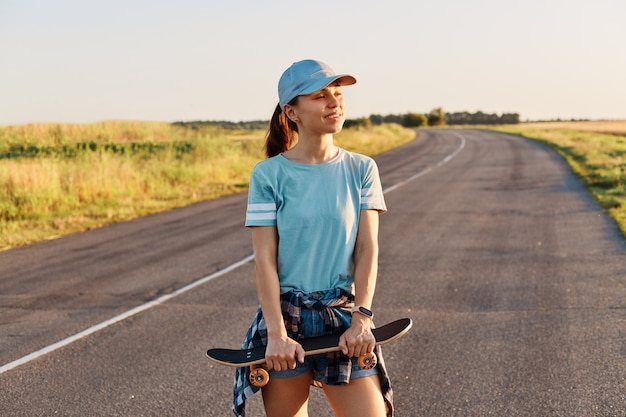 Bella donna che indossa maglietta blu e visiera in piedi con lo skateboard in mano e distoglie lo sguardo con un sorriso a trentadue denti ed emozioni positive, stile di vita attivo