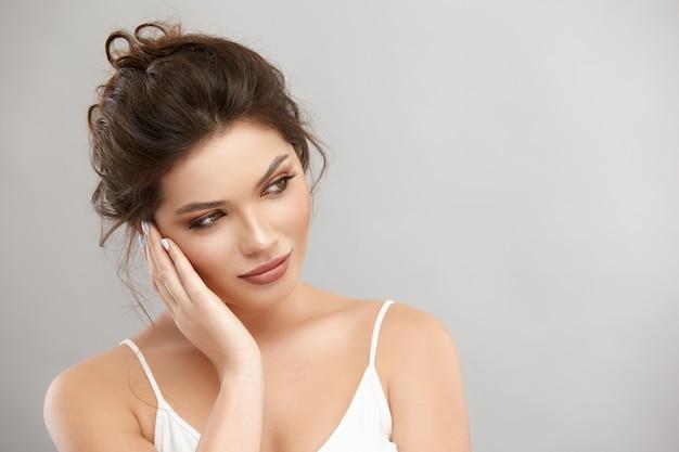 Bella femmina con pelle pulita perfetta che guarda al lato con il braccio vicino al viso