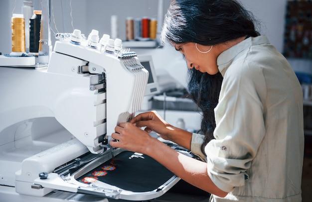 La bella lavoratrice è nella fabbrica di cucito vicino alla macchina.