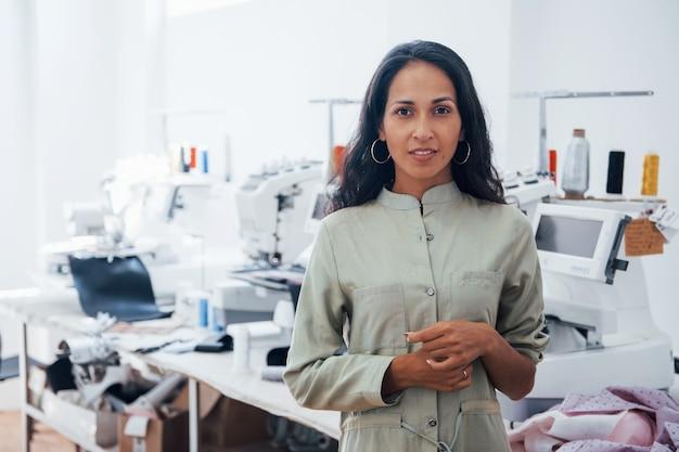 La bella lavoratrice è nella fabbrica di cucito durante il giorno.