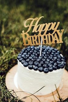 Torta per bambini bella cagliata festiva con mirtilli con la scritta happy birthday.