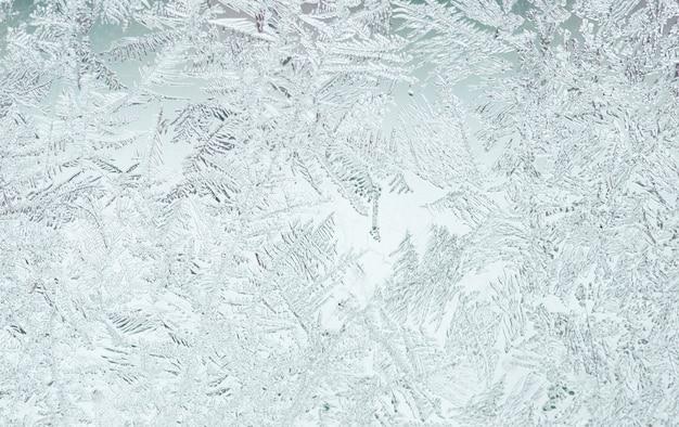 Bello modello gelido festivo con fiocchi di neve bianchi su sfondo blu su vetro