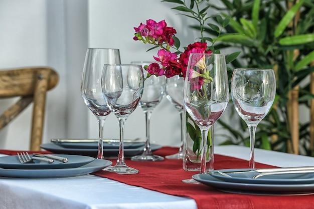 Bella tavola festiva e fiori nella stanza luminosa