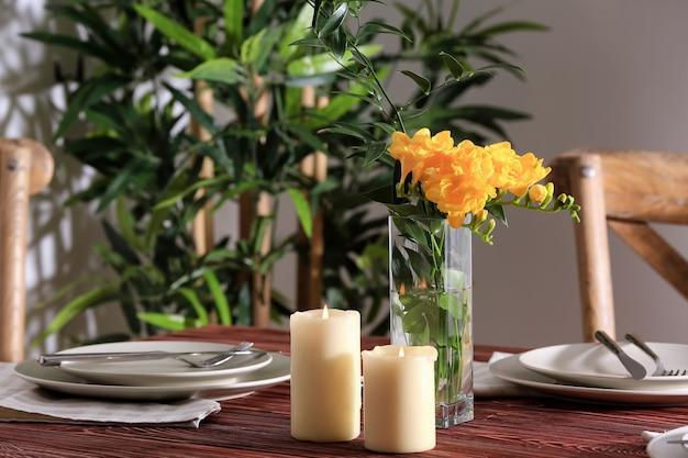 Bella tavola festiva e vaso con fiori in camera luminosa