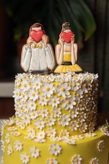 Bella torta gialla festiva con uomo e donna decorativi che si coprono il viso di cuori