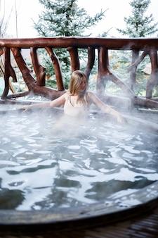 Bella figura donna in costume da bagno. ragazza in piscina con acqua calda in terrazza, trattamenti spa per il corpo. jacuzzi all'aperto. jacuzzi con una ragazza. relax all'aria aperta, benessere. cottage con vasca idromassaggio