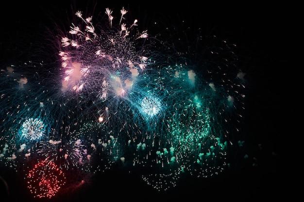 Bellissimi fuochi d'artificio di notte. scoppio colorato sul cielo nero. traccia di luce con scoppio luminoso e scintille da fuochi d'artificio che esplodono nel cielo notturno. esposizione prolungata