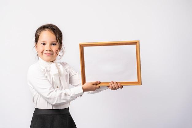 Bella ragazza della scuola elementare in una camicia bianca tiene un foglio bianco per l'iscrizione.