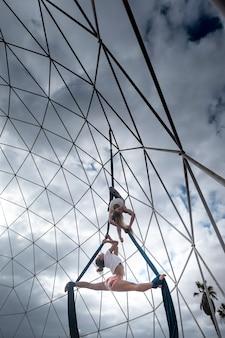 Bel corpo in forma persone giovani ragazze che fanno esercizi in stile acrobata da circo sospesi in aria con corde