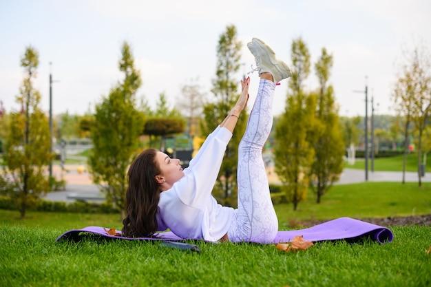 Una bella donna in forma sdraiata sul tappetino sportivo e fa crunch addominali, trazioni e allungamenti nel parco verde della città