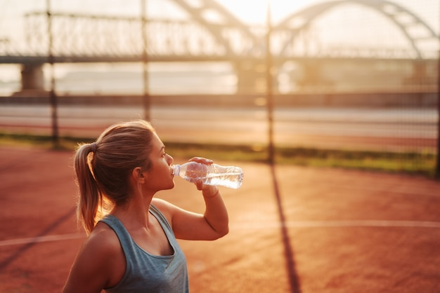 Acqua potabile della ragazza sportiva di bella misura dopo l'addestramento duro di primo mattino. allenarsi fuori e distogliere lo sguardo.