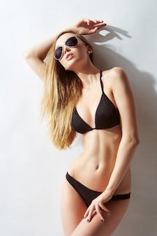 Donna bella, in forma e sportiva in costume da bagno. perdita di grasso, liposuzione e concetto di rimozione della cellulite.