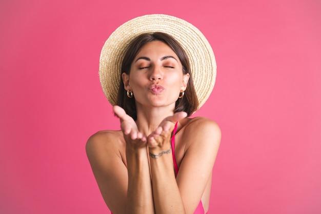 Bella donna sportiva abbronzata in forma in bikini e cappello di paglia sul rosa
