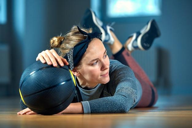 Bella donna in forma in abiti sportivi in posa mentre giaceva sul pavimento con il basket davanti alla finestra in palestra stile di vita della ragazza sana e concetto di sport