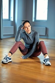 Bella donna in forma in abiti sportivi in posa mentre era seduto sul pavimento davanti alla finestra in palestra
