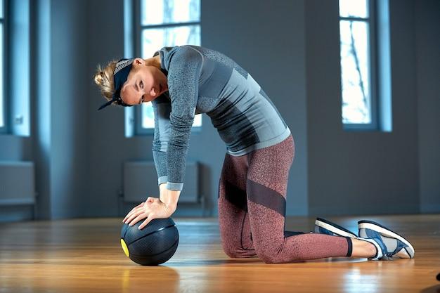 Bella donna in forma in abiti sportivi in posa mentre era seduto sul pavimento con palla fitness davanti alla finestra in palestra stile di vita della ragazza sana e concetto di sport