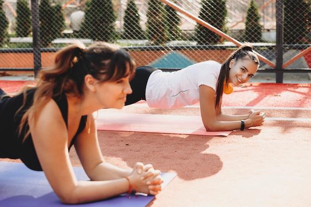 Belle donne in forma che aiutano a perdere peso esercizi con la sua ragazza plus size all'aperto ina sport park al mattino.