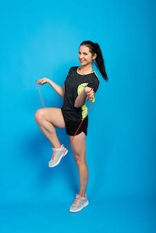 Bella donna di forma fisica che salta la corda, girato in studio