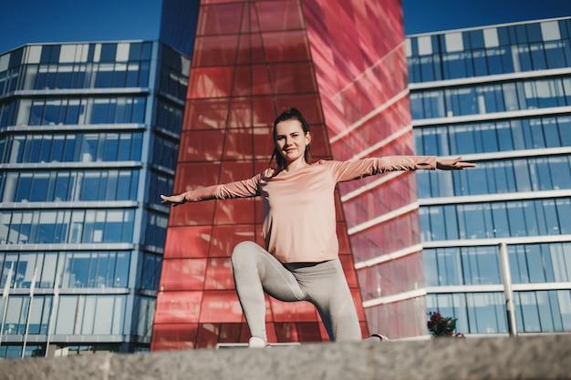 Bella ragazza di forma fisica che posa all'aperto. donna sportiva con un corpo perfetto, uno stile di vita sano e un concetto di cura del corpo