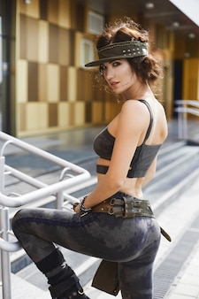 Ragazza bellissima modella fitness con corpo sexy perfetto in abito alla moda con modello militare in posa all'aperto a fondo urbano