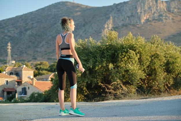 Bella ragazza corridore fitness utilizzando smartphone e cuffie che ascoltano musica. uno stile di vita sano e attivo negli adolescenti sfondo soleggiata giornata estiva in montagna