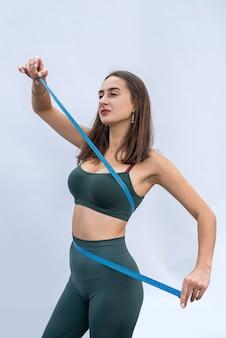 Bella giovane donna di sport di forma fisica che misura il suo corpo con nastro adesivo di misura sopra su fondo grigio. uno stile di vita sano