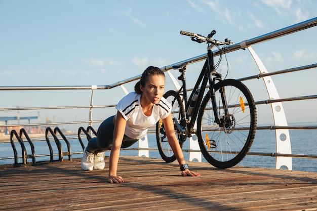 Bella donna fitness facendo esercizio di plancia in spiaggia, in sella a una bicicletta