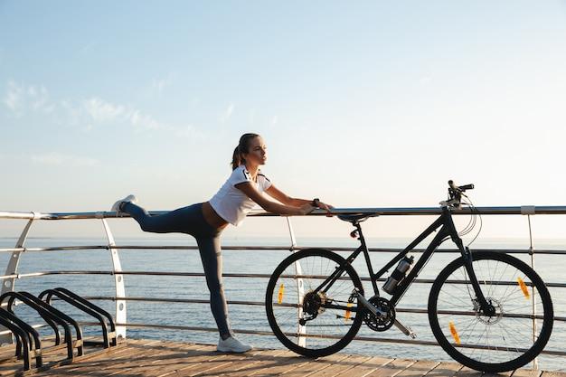 Bella donna fitness facendo esercizi di stretching in spiaggia, in sella a una bicicletta