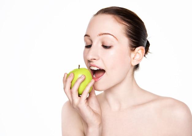Bella donna di forma fisica che mangia mela sana su bianco