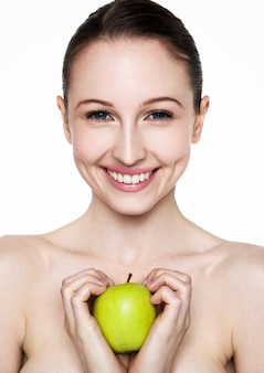Bella donna di forma fisica che tiene mela sana su fondo bianco