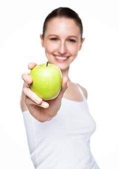 Bella donna di forma fisica che tiene mela sana su bianco