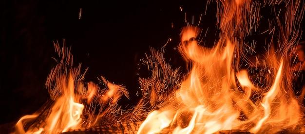 Bella fiamma di falò con scintille con tonques di fuoco sullo sfondo del cielo notturno isolato