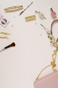 Bella disposizione piatta con fiori di mela, cosmetici e altri accessori. mockup di blogger creativo o di bellezza, sfondo beige, spazio di copia