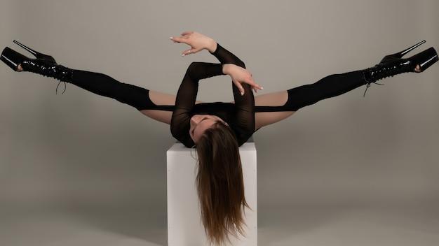 Ballerino del palo di bella ragazza flessibile con i tacchi alti in posa in studio