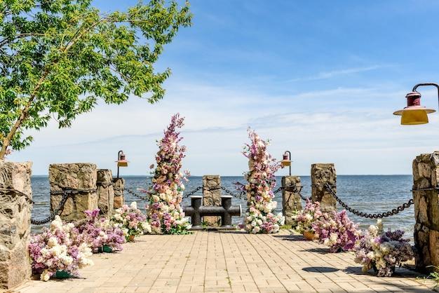 Bellissima composizione floreale per un matrimonio in trasferta sulla costa oceanica. solenne cerimonia di pittura dello sposo e della sposa
