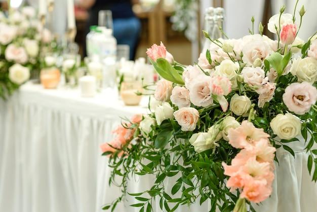 Bellissime composizioni floreali nel ristorante per la cerimonia nuziale. cerimonia solenne di dipingere lo sposo e la sposa