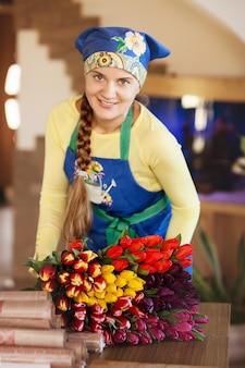La bella ragazza del fiorista tiene un enorme mazzo di tulipani in un negozio di fiori
