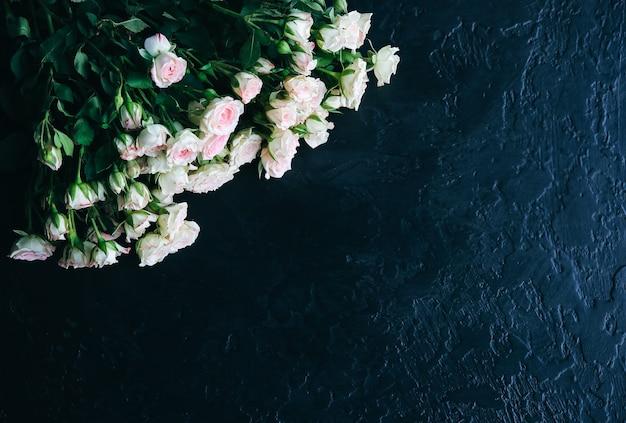 Bellissimi fiori su sfondo nero. mazzo di rose. posa piatta perfetta. cartolina di festa della madre felice. saluto per la giornata internazionale della donna. idea elegante per pubblicità o promozione.