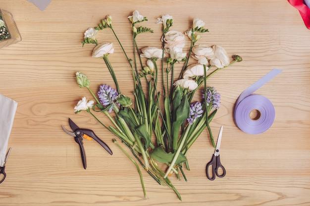 Bellissimi fiori e attrezzature fiorista sulla tavola di legno