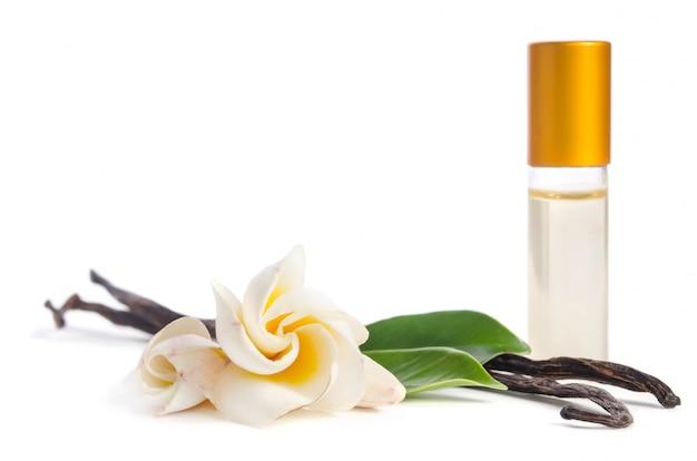 Bei fiori, vaniglia naturale e bottiglie con oli per pelle isolata su bianco