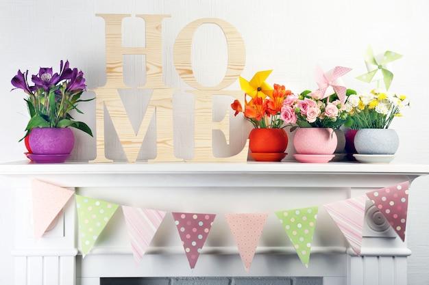 Bellissimi fiori in vaso di fiori ornamentali sul caminetto