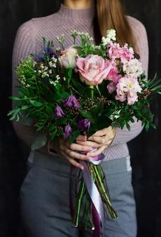 Il mazzo rustico dei bei fiori nelle mani della donna