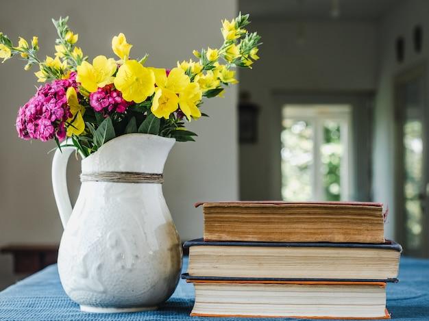 Bei vaso e libri di fiori che si trovano su una tavola di legno